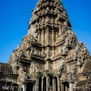The main temple at Angkor Wat with a gentle flutter of birds dancing around its ancient carvings.