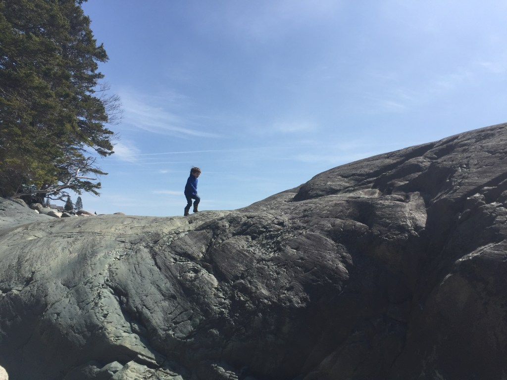 photo of young boy on rock ledge at Acadia National Park