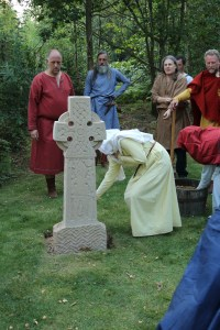Gytha adds a handful of soil to the base of Kim's cross. Everyone present added theirs before it was filled in.