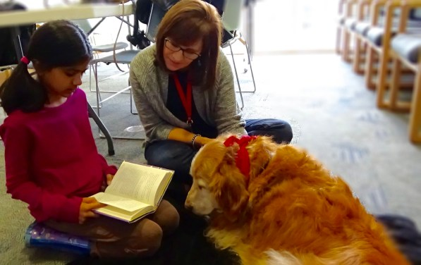Onamika Dey, 9 years old, reading a chapter to book to therapy dog, Sedona, at the Happy Tails/READing Paws event, hosted by the Atlanta Public Library, Bulkhead location. (Photo: Alicia Buster/Full Sail University)