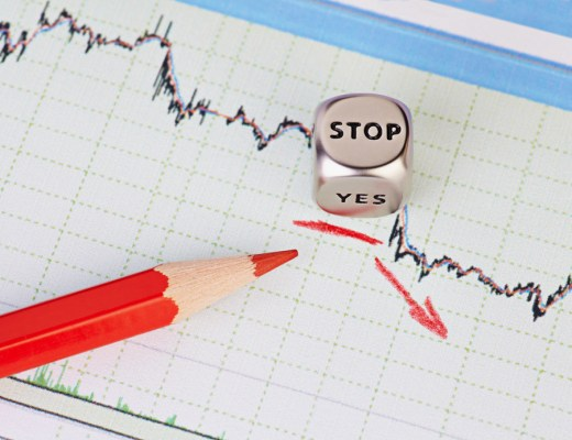 Downtrend financial market chart , red pencil, red arrow and dices cube with the word STOP. Selective focus