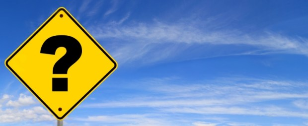 Road sign with question mark, against panoramic blue sky.