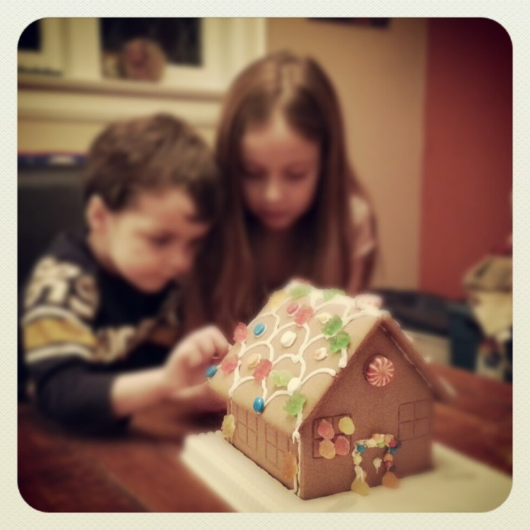 Kids making Christmas gingerbread house