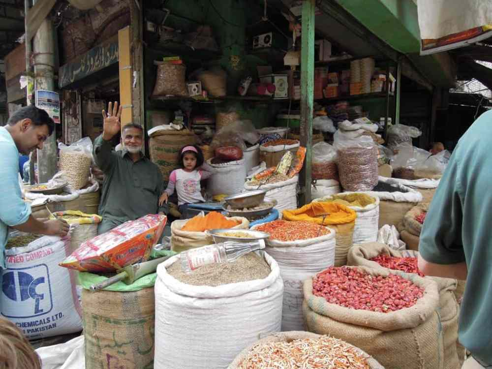 Bags of colorful and pungent spices surround an outdoor stall vendor in Lahore, Pakistan