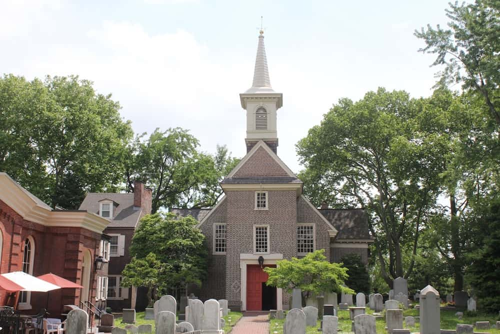 Historic brick church is set behind a weathered graveyard.