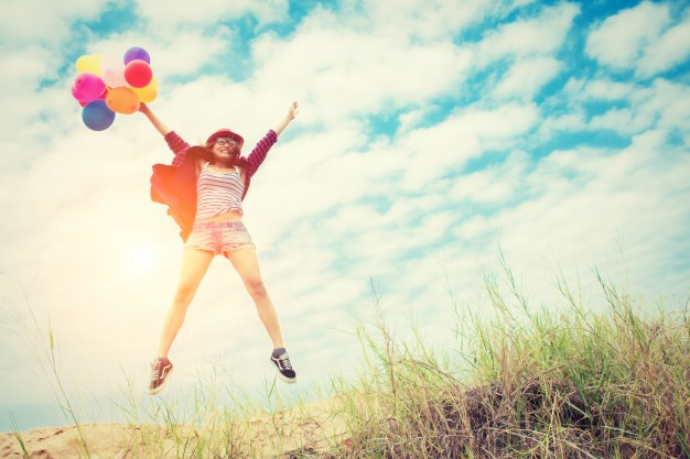 girl-jumping--in-the-beach-with-colored-balloons_1150-15