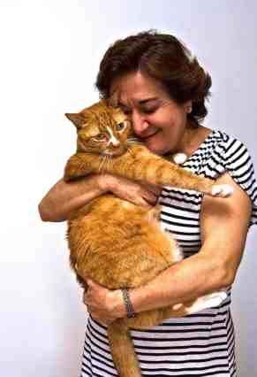 An older lady in a black and white striped shirt holding an orange cat.