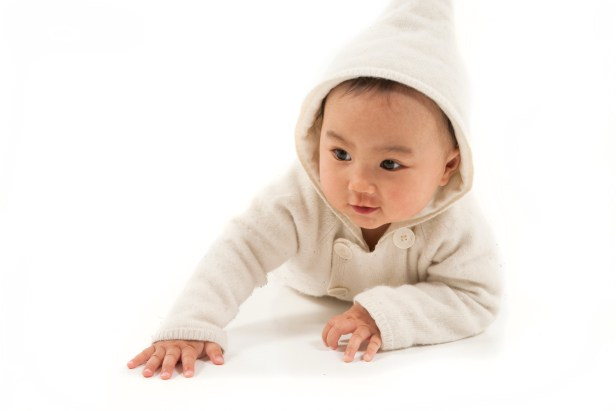 asian baby crawling with white hoodie in studio