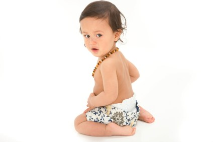 bewildered baby boy from back in studio photoshoot topless and white short