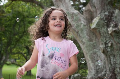 Young curly girl playing with bubbles in One Tree Hill Park, Auckland, New Zealand. Professional portrait by Anais Chaine Photographer