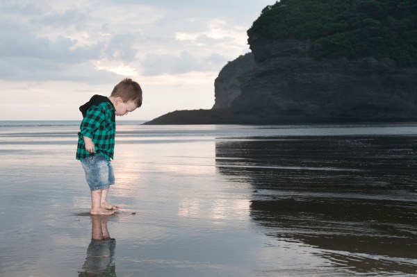 Bethells beach, Reflection on send child little boy photoshoot by Anais Photography, Auckland