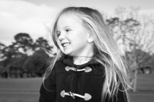 Professional portrait of young girl smiling in movement black and white in One Tree hill Park, Auckland, New Zealand