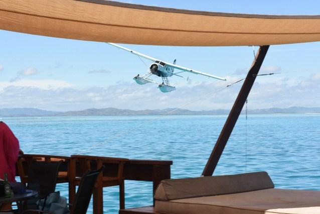 Seaplane flying in a beautiful sea landscape in front of Cloud 9 bar island Fiji