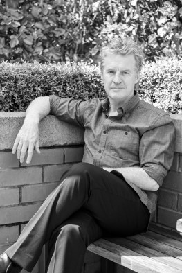 Black and white Don McGlashan seating in a garden lean on the wall