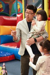 Father hold his daughter and pointing on a game