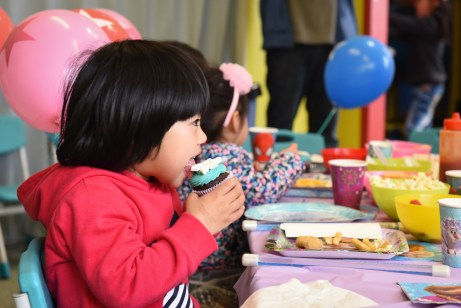 child liking the icing of a cup cake with tongue out