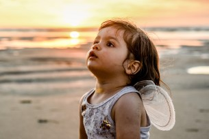 Baby Ainoha in tiny wings against sunset on the beach