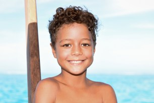 A cute little boy smiles at the camera aboard Cloud 9 in Fiji
