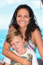 Mother and son smile at the camera aboard Cloud 9 in Fiji