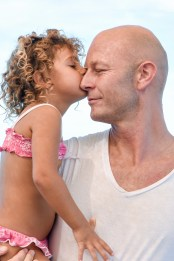 A daughter kisses her father on the cheek aboard Cloud 9 Fiji