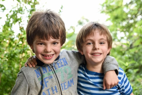 two brothers looking at the camera laughing while holding at each others in a park in france