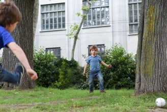two young boys playing soccer in a park with the goal between two trees