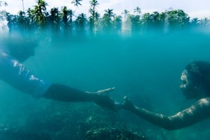 over under shot with couple's arm reaching towards each others in the water and palm trees outside