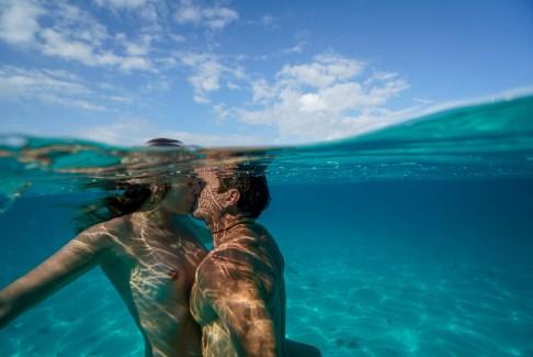 Nude couple kissing underwater in Fiji