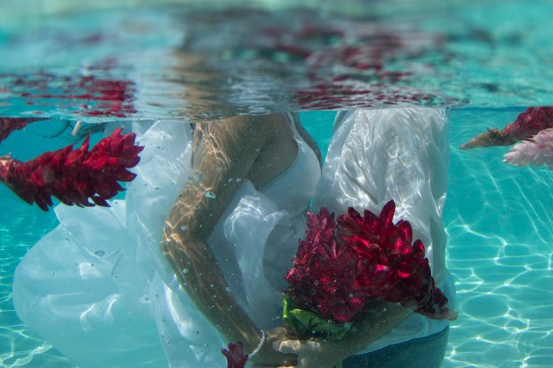 couple holding the bouquet under the water in the pool in Fiji by Anais Photography