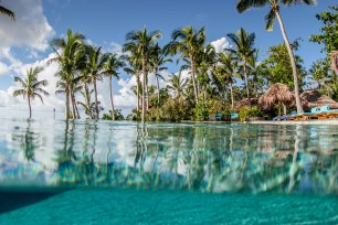 over under shot with Tokoriki swimming pool in the bottom and palm tress in the top in Fiji by Anais Photography