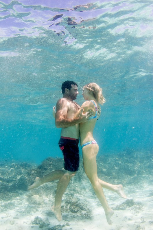 Couple holding eachother hugging in verticale position underwater Cloud 9 in the Mamanuca islands in Fiji