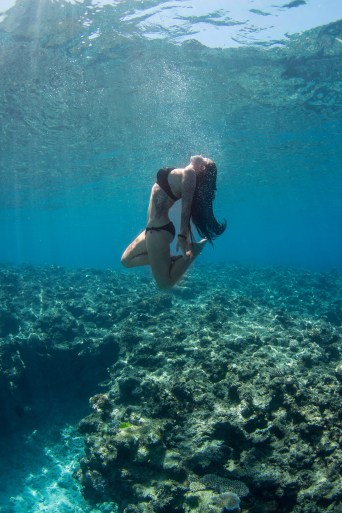 Woman underwater by a coral wall