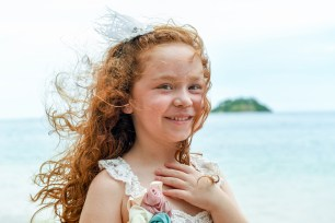 Red head girl smiles at camera in family photoshoot in Malolo Island Resort Fiji