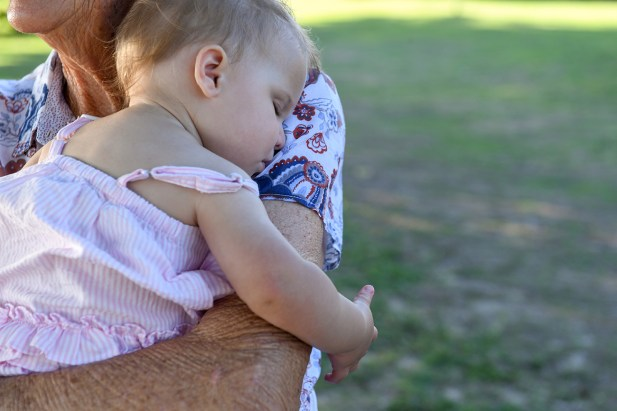 Cute baby asleep on grandfather's arm in family photoshoot in Natadola beach Fiji
