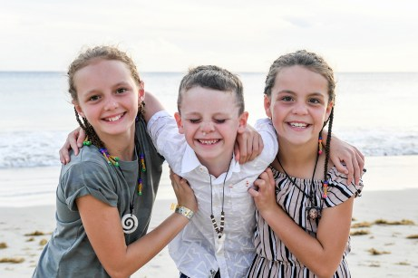 Cute young sisters and brother grin in family photography Natadola beach