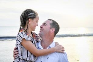 Braided daughter and father look into each others eyes in family beach photography