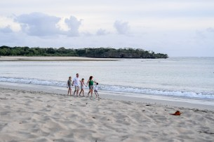 Wide shot of family strolling on beach in Fiji Natadola