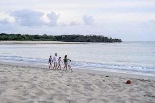 Wide shot of family strolling on beach in Fiji Natadola