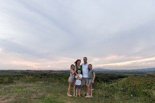 Cute family stands against sunset in the hills in Fiji