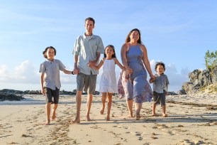 Beautiful family strolling on the beach in family photoshoot