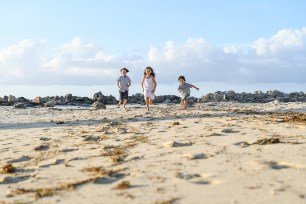 Wideshot of 3 cute kids running on the beach