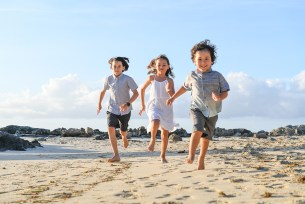 3 cute siblings running on Fiji sandy beach in Malolo village