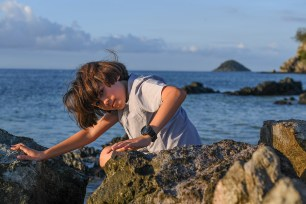 Cute boy makes funny pose against the sea in Malolo Fiji