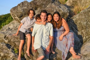 Cute mixed race family pose for a photoshoot against a rock in Fiji