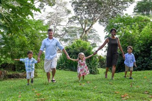 Mixed race family hold hands while walking on lawn in Fiji family vacation