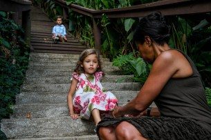 Mom puts shoes on her daughter at bottom of steps during family vacation