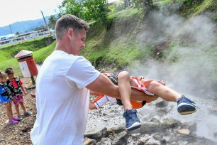 Dad carries son over hot water spring in Fiji family vacation