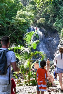 Family on vacation in Fiji walk towards waterfall