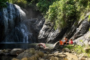 Family seated by river watching waterfall during family vacation in Fiji