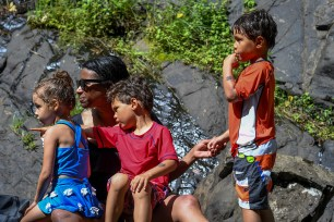 Family sit against rock in Fiji family vacation
